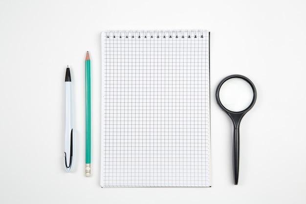 Cuaderno de papel con pluma o lápiz sobre fondo blanco aislado. vista superior. aplanada bosquejo Foto Premium