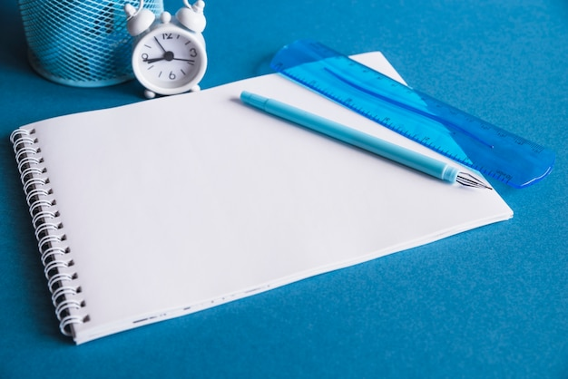 Cuaderno de papel vacío con bolígrafo y reloj Foto gratis