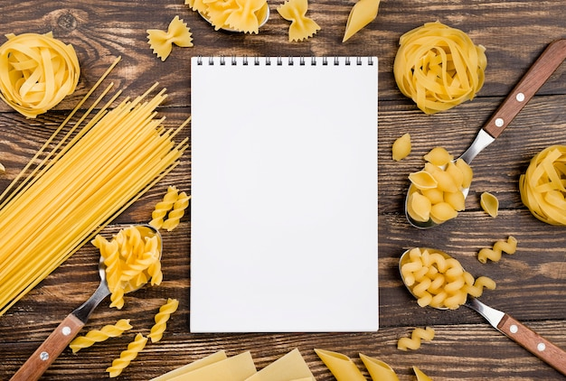 Cuaderno y pasta en cucharas Foto gratis