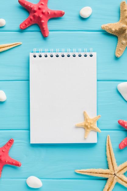 Cuaderno plano laico con estrellas de mar Foto gratis