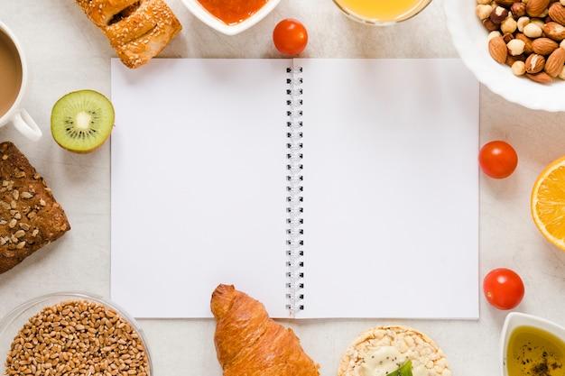 Cuaderno plano con marco de comida Foto gratis