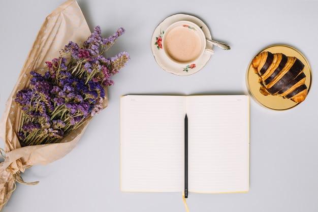 Cuaderno con ramo de flores y croissant. Foto gratis