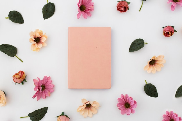 Cuaderno rosa con estampado de flores alrededor sobre fondo blanco Foto gratis
