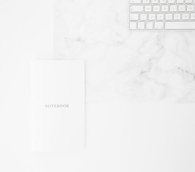 Cuaderno y teclado en el escritorio contra el fondo blanco Foto gratis