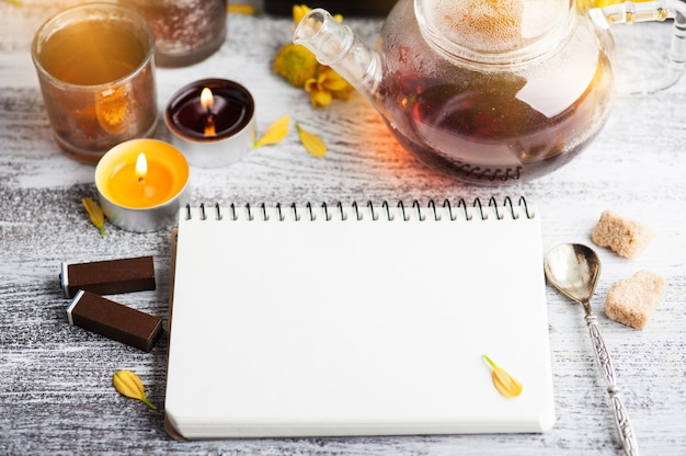 Cuaderno vacío con velas encendidas y tetera Foto Premium