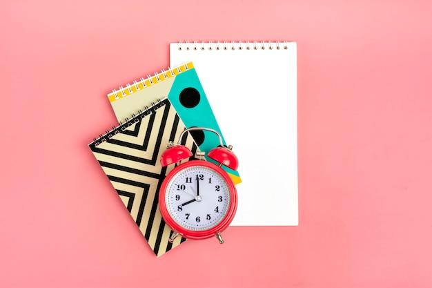 Cuadernos geométricos y reloj despertador en rosa estacionario, concepto de regreso a la escuela lay flat Foto Premium