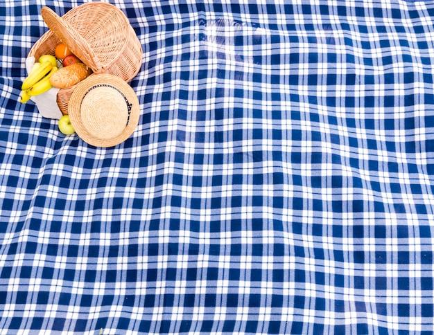 Cuadros azules a cuadros con sombrero de paja y fondo de cesta de picnic Foto gratis