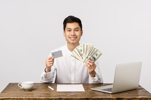 Cual es tu eleccion. apuesto empresario rico y exitoso, hombre exitoso mostrando mucho dinero en efectivo, dólares y tarjeta de crédito, sonriendo complacido, consejos para mantener el depósito de dinero elegir su banco Foto Premium