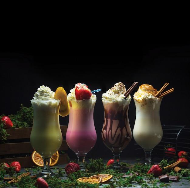 Cuatro batidos de cóctel diferentes con crema láctea en la parte superior Foto gratis