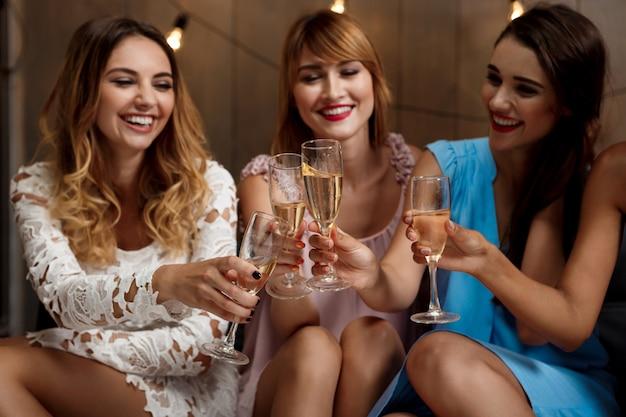 Cuatro chicas guapas tintineo de copas con champán en la fiesta. | Foto  Gratis
