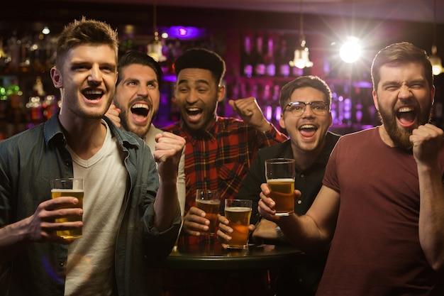 Cuatro hombres felices sosteniendo jarras de cerveza y gesticulando Foto gratis