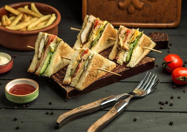 Cuatro porciones pequeñas de sándwich club de pollo en brochetas de bambú Foto gratis