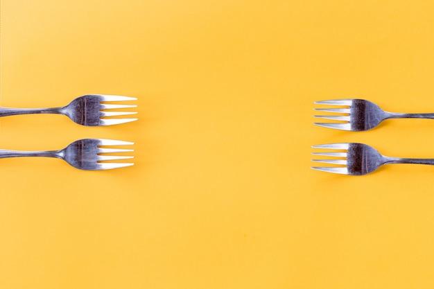 Cuatro tenedores sobre fondo amarillo Foto Premium
