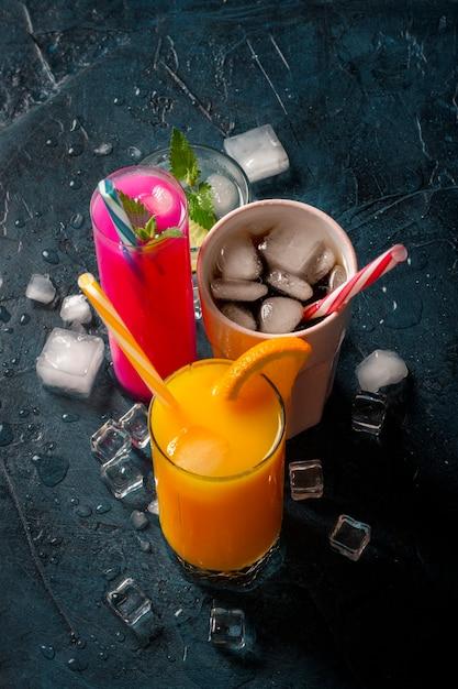 Cuatro tipos de bebidas refrescantes con hielo sobre una superficie azul oscura y cubitos de hielo. Foto Premium