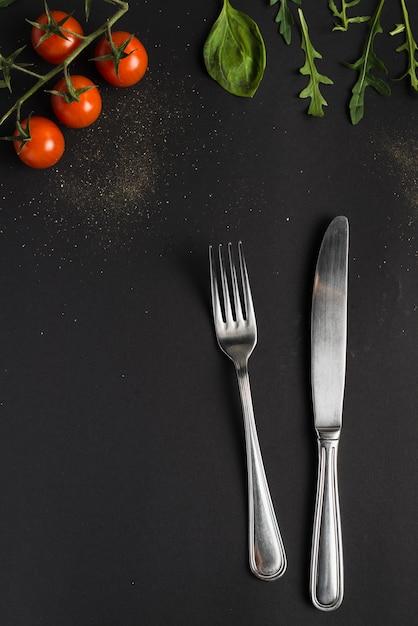 Cubiertos cerca de tomates y albahaca Foto Premium