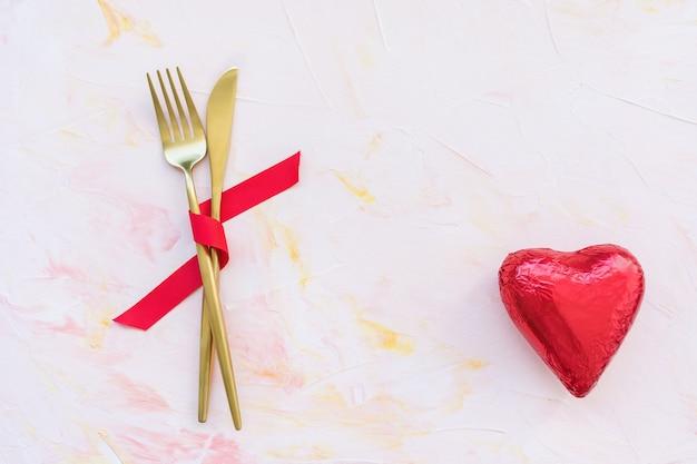 Cubiertos dorados en cinta roja y corazón en rosa Foto Premium
