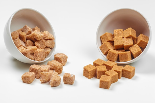 Cubitos de azúcar moreno de caña aislados Foto Premium