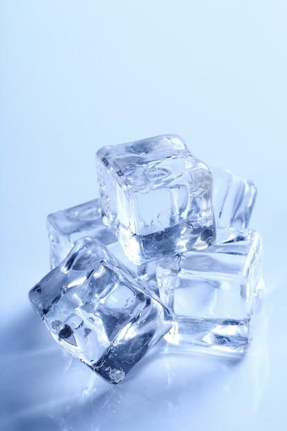Cubitos de hielo aislados en azul Foto gratis