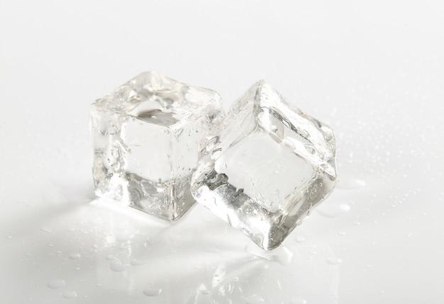 Cubitos de hielo en mesa blanca Foto gratis