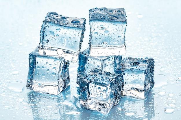 Cubitos de hielo sobre fondo azul. Foto Premium