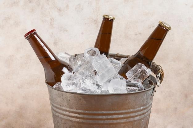 Cubo de alto ángulo con cubitos de hielo y botellas de cerveza. Foto gratis