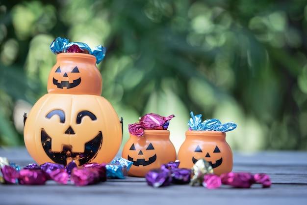 Cubo de halloween jack-o-lantern con derramar dulces Foto Premium