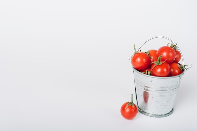 Cubo lleno de tomates jugosos rojos sobre fondo blanco Foto gratis
