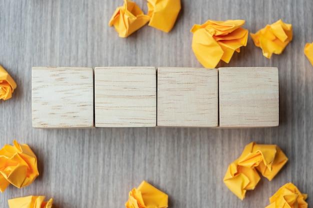 Cubos de madera vacíos con papel desmenuzado en mesa de madera Foto Premium