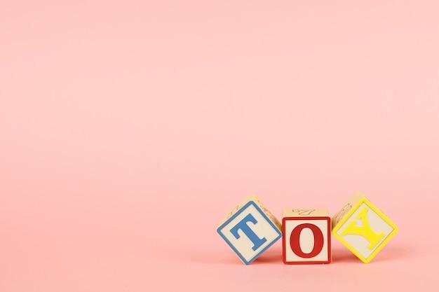 Cubos rosados y de colores con letras con la inscripción toy Foto Premium