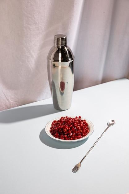 Cuchara de cóctel con coctelera y plato de semillas de granada sobre escritorio blanco Foto gratis