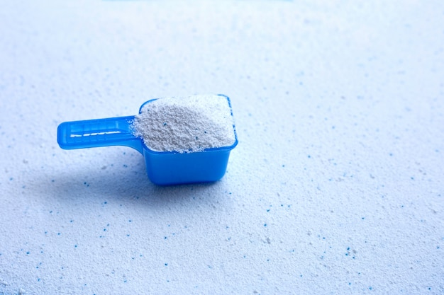 Cuchara dosificadora azul con detergente en polvo. Foto Premium