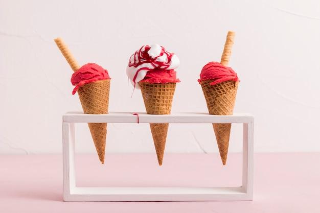 Cuchara de helado rojo en conos con almíbar y paja de waffle en el stand Foto gratis