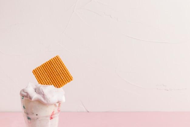 Cuchara de hielo cremoso con paja de waffle en un recipiente de plástico Foto gratis