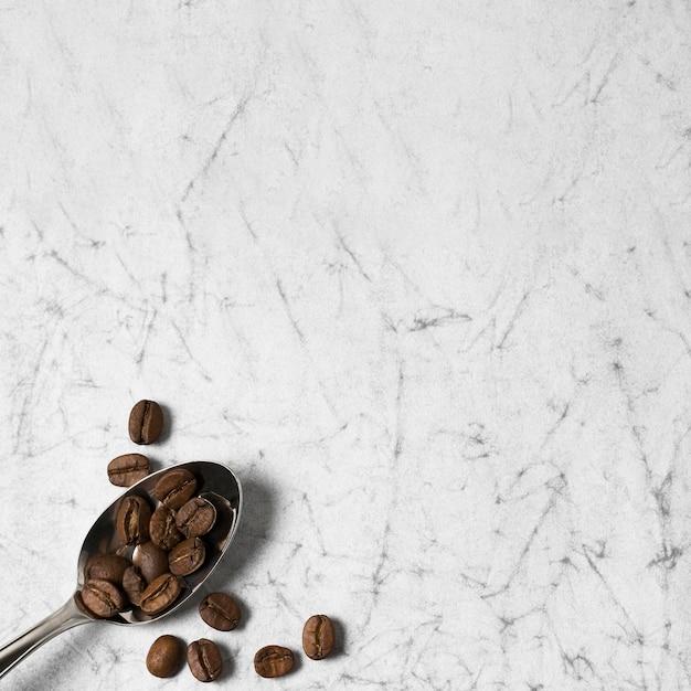 Cuchara llena de granos de café y espacio de copia Foto gratis