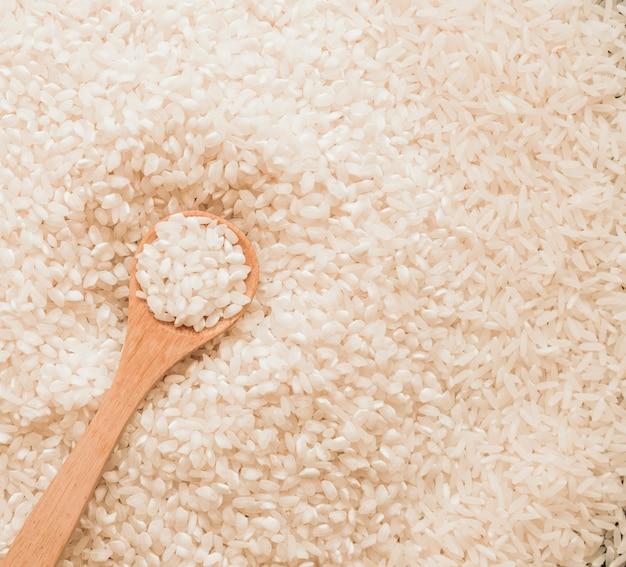Cuchara de madera en granos de arroz blanco sin cocer Foto gratis