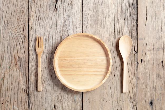 Cuchara de madera y placa de madera sobre fondo de mesa de madera vieja Foto Premium