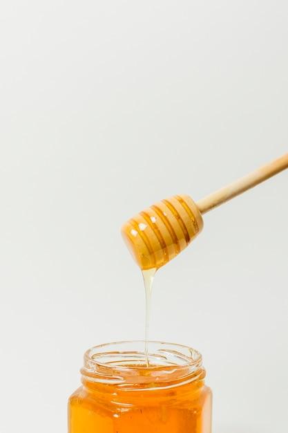 Cuchara de miel sobre tarro Foto gratis