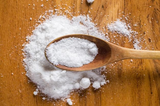 Cuchara y montón de sal sobre la mesa Foto gratis