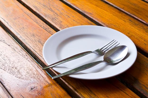 Cuchara y tenedor sobre un plato Foto gratis