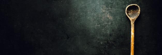 Cuchara vieja en la mesa oscura Foto gratis