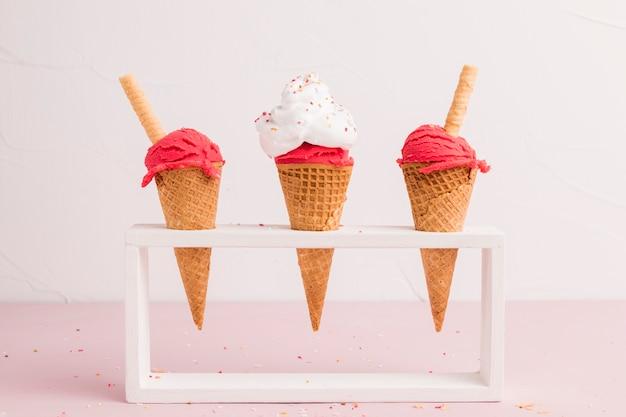 Cucharada de helado congelado rojo en conos con paja de gofres Foto gratis