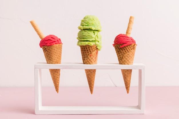 Cucharada de helado fresco en conos con paja de waffle en soporte Foto gratis