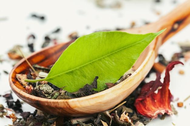 Cucharadita colmada de té seco en blanco, primer plano Foto Premium