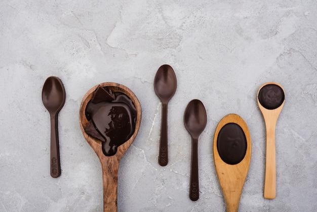 Cucharas de madera con chocolate derretido Foto gratis