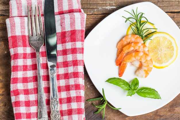 Cuchillo y tenedor al lado de un plato con gambas cocidas for Plato tenedor y cuchillo