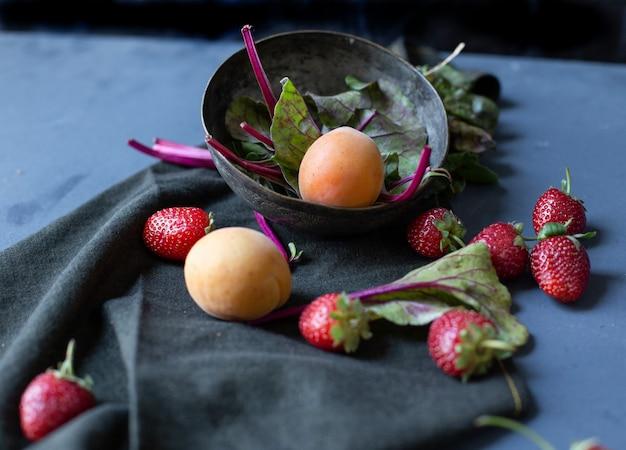 Cuenco con albaricoques y espinacas adentro y fresas afuera. Foto gratis