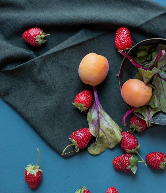 Cuenco con albaricoques y espinacas dentro y fresas afuera sobre una estera negra. Foto gratis