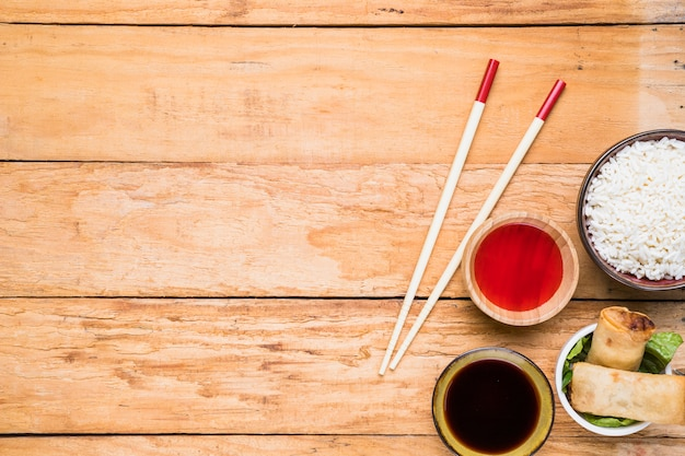 Cuenco de arroz blanco; rollitos de primavera y salsas con palillos en mesa de madera Foto gratis