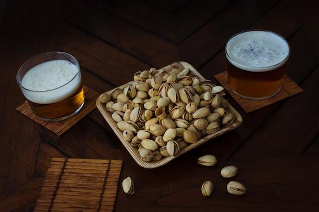 Cuenco de bambú lleno de pistachos y dos vasos de cerveza en un pub. mesa de madera. fiesta de verano de celebración. Foto Premium