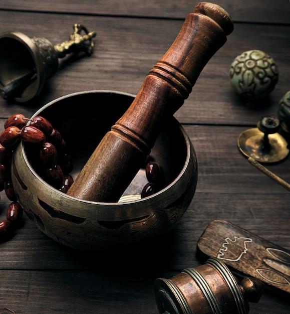 Cuenco cantor de cobre y un palo de madera en mesa marrón Foto Premium